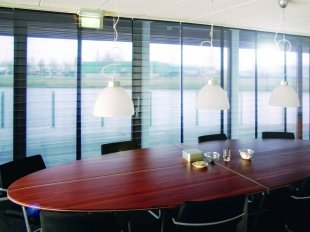 Panel glide system with pleated film panels for stylish sun protection in conference rooms